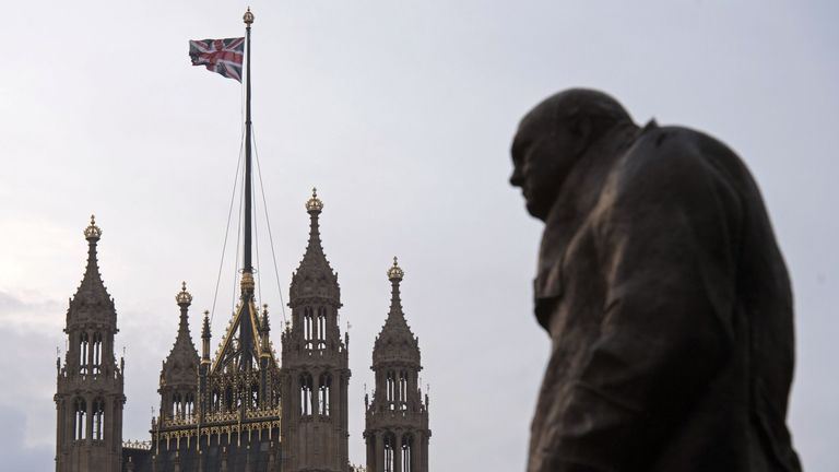 A Union Jack flies from the roof of the House of Commons with Churchill's statue in the foreground