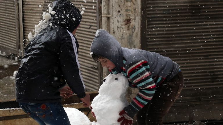 Syrian children make a snow man in the town of Maaret al-Numan, in Syria's northern province of Idlib, on December 21, 2016. Rebels and civilians who have sought refuge in the opposition-held province of Idlib, most recently from second city Aleppo, say they are suffering from skyrocketing prices and overpopulation. At least 25,000 people, including rebel fighters, have left east Aleppo since last week under an evacuation deal that will see the city come under full government control