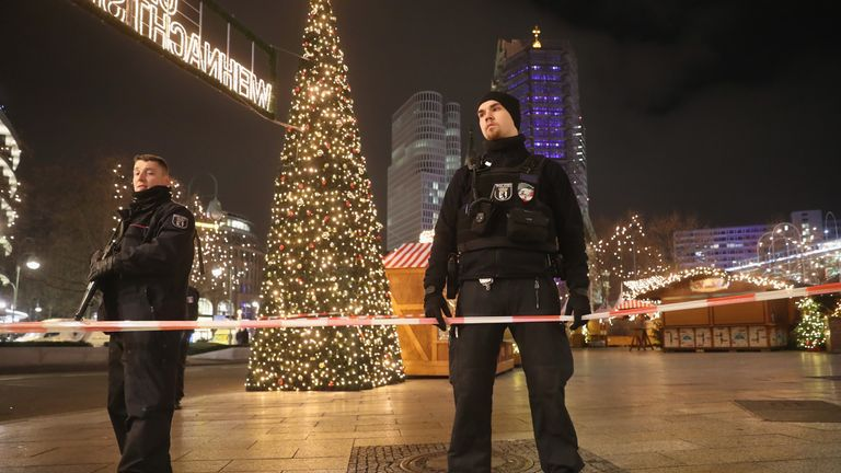 Security stand and guard the area after a lorry truck ploughed through a Christmas market in Berlin, Germany.