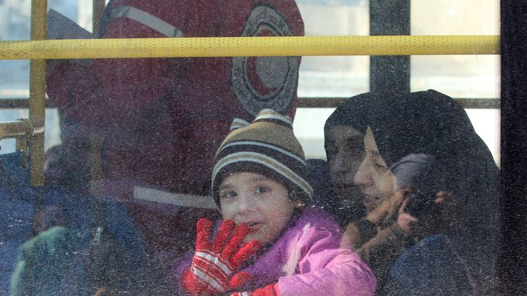 A child waves from inside a bus as she is evacuated from rebel-held areas in Aleppo
