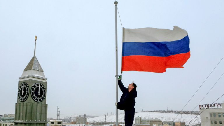 A worker lowers the Russian national flag to half-mast on a roof of the city administration building
