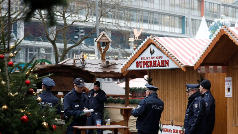 Policemen are seen near the area where a truck which ploughed into a crowded Christmas market