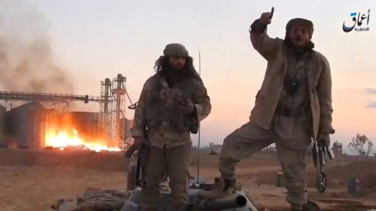 A still image taken from a video released by Islamic State-affiliated Amaq news agency, said to be in Palmyra, on December 11, 2016, purports to show Islamic State fighters in front of silos on fire and said to have been taken over by them