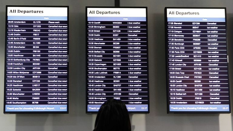 An airport worker looks at departure boards at Edinburgh Airport