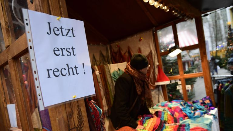 "A sign reading ""Now more than ever"" is fixed at a booth at the Christmas market near the Kaiser Wilhelm Memorial Church in Berlin"