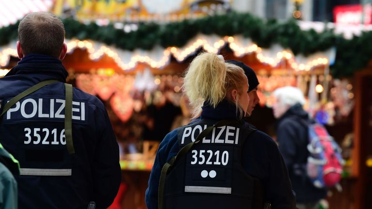 A policeman and a policewoman walk at the Christmas market near in Berlin following the lorry attack