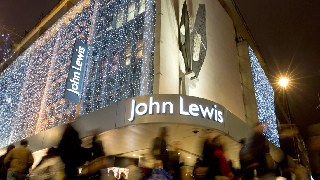 Pedestrians walk past a John Lewis store on Oxford Street, London, Britain, December 15, 2013