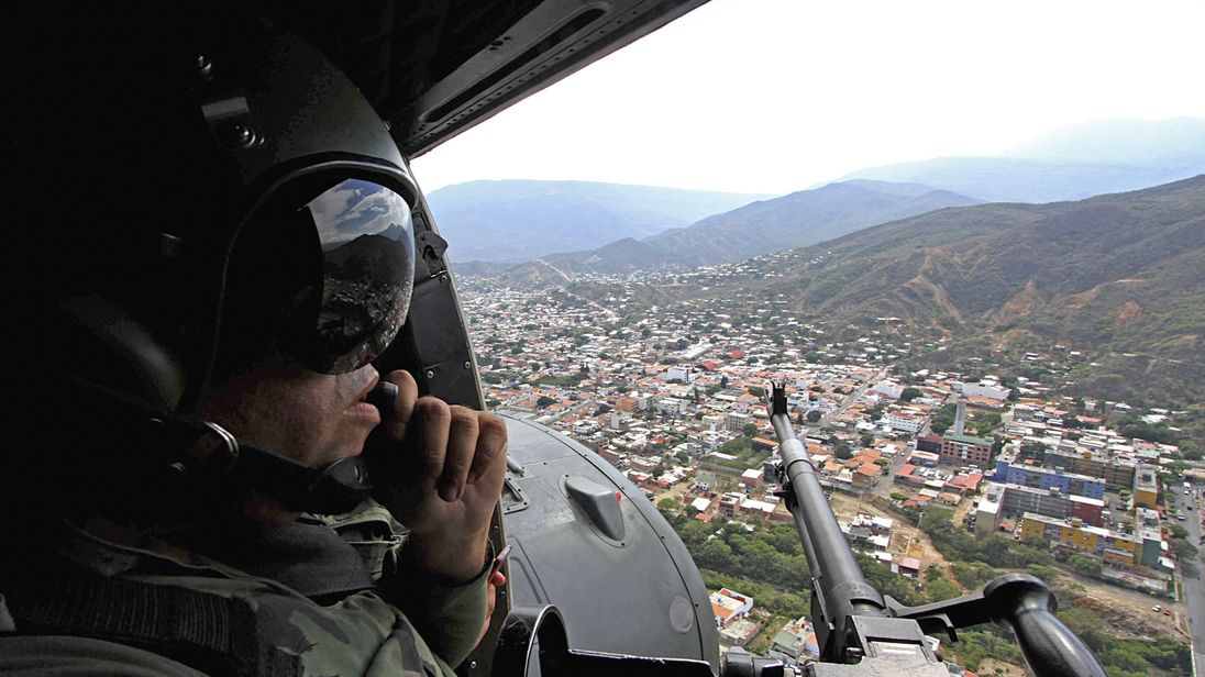 A Venezuelan gunner mans his machine gun on board a helicopter