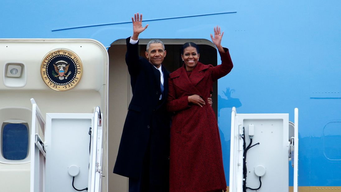 Former president Barack Obama waves with his wife Michelle as they board Special Air Mission 28000