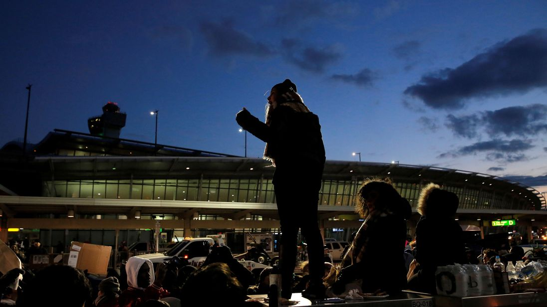 People gather at Terminal 4 during a protest at JFK International Airport in Queens