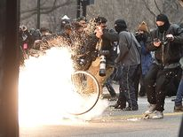 A flash-bang grenade explodes during clashes between riot police and protesters