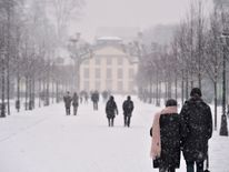 People walk in the snowfall in a park in Strasbourg, eastern France
