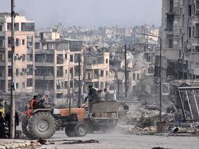 Workers clear debris in a former rebel-held district of Aleppo