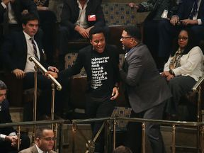A protester is removed from the gallery