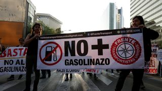 Demonstrators hold a banner during a protest against a fuel price hike in Mexico City