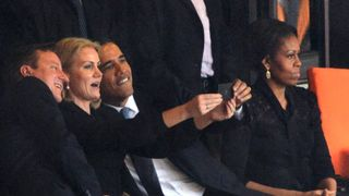 US President Barack Obama (R) and British Prime Minister David Cameron pose for a selfie picture with Denmark's Prime Minister Helle Thorning Schmidt (C) next to US First Lady Michelle Obama (R) during the memorial service of South African former president Nelson Mandela at the FNB Stadium (Soccer City) in Johannesburg on December 10, 2013