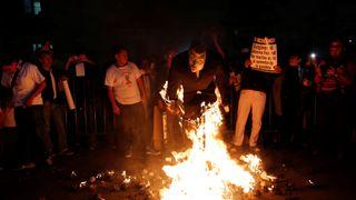 Demonstrators burn a figure of U.S. President-elect Donald Trump