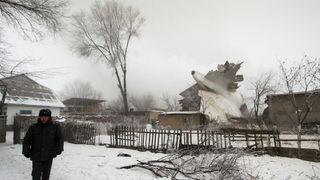 A policeman guards an area at the crash site of a Turkish cargo jet near Kyrgyzstan's Manas airport outside Bishkek