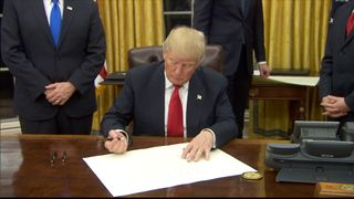 President Donald Trump signs an executive orders calling for the repeal of Obamacare