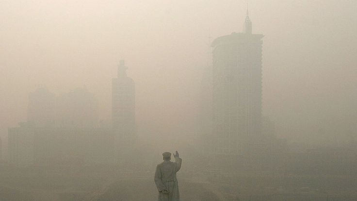 Heavy fog envelopes Chengdu in front of a Mao Zedong statue