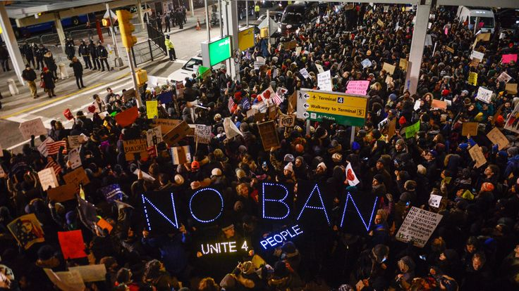 Demonstrators hold signs during a rally against a ban on Muslim immigration at San Francisco International Airport