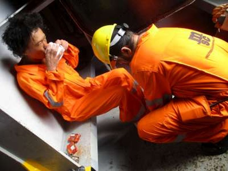 The man is given hot drinks after being rescued by container ship MSC Damla