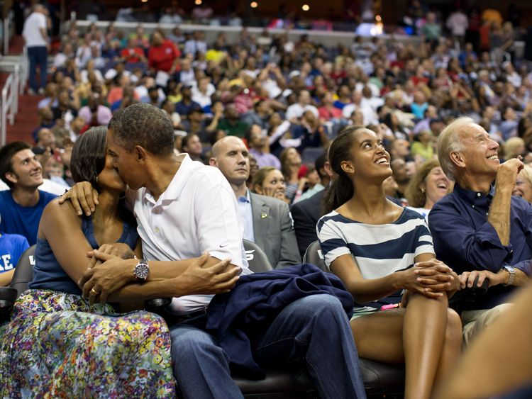 Barack Obama kisses his wife Michelle at a basketball game next to daughter Malia and Vice President Joe Biden
