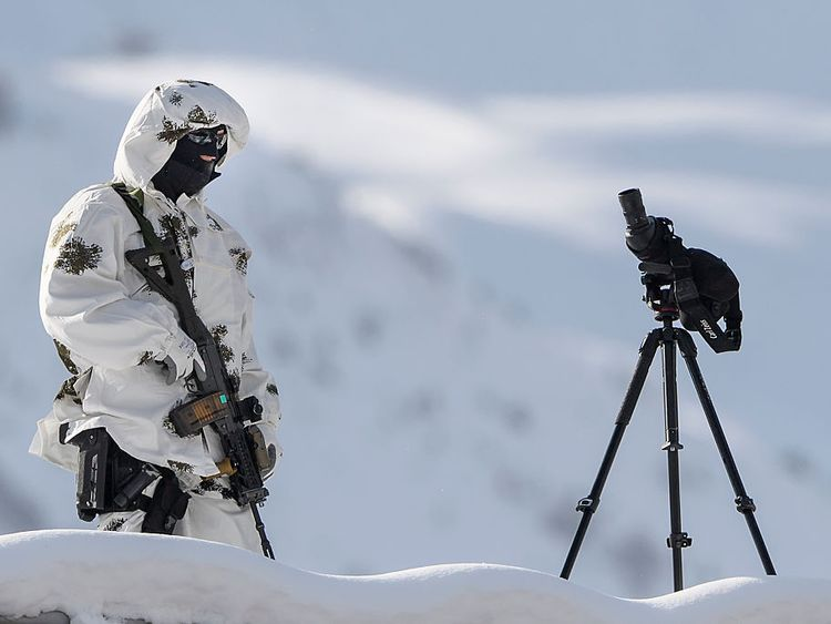 A police sniper stands guard over the Davos Congress Centre