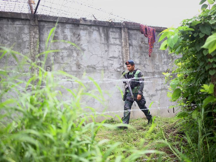 An armed policeman patrols along the perimeter fence of the district jail