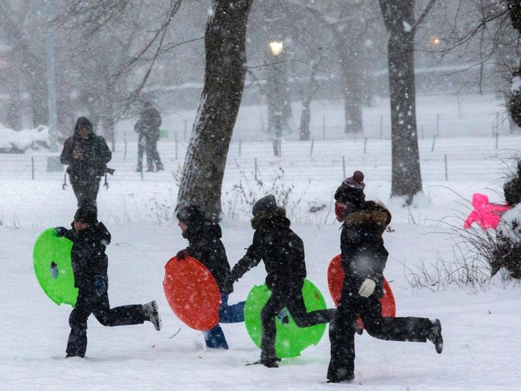 Children play under a snowfall in Central Park during a winter storm on January 7, 2017 in New York