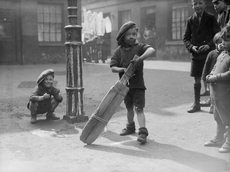 9th April 1934: A group of children in a slum area of London's King's Cross play an improvised game of cricket with a lamppost as a wicket and a bat tied together with string