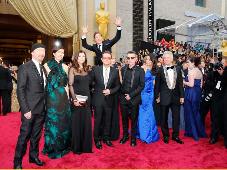 Actor Benedict Cumberbatch jumps behind U2 at the 86th Academy Awards in Hollywood, California March 2, 2014