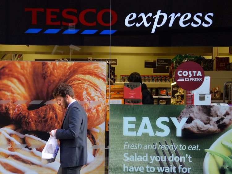 A customer passes a branch of the Tesco Express convenience store in central London December 2013
