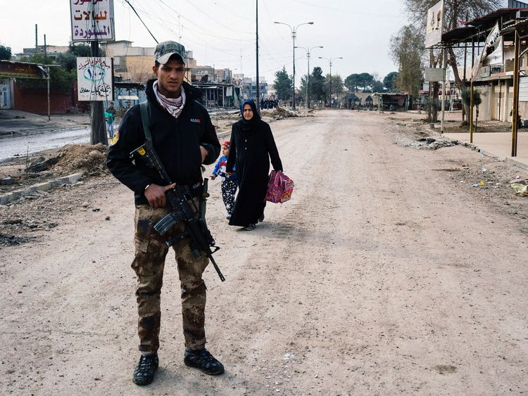 An Iraqi special forces Counter Terrorism Service (CTS) member stands guard in a street in Mosul's al-Zahraa neighborhood on January 8, 2017, as a woman and her child flee during an ongoing military operation against Islamic State (IS) group militants. Elite Iraqi forces battling the Islamic State group in eastern Mosul reached the Tigris River that splits the city in two for the first time, a spokesman said