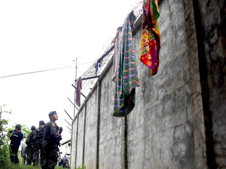 Armed police patrol along the perimeter fence of the district jail