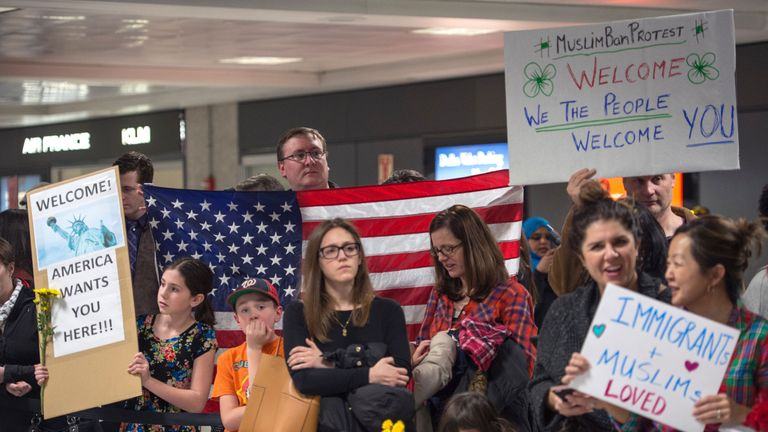 Protesters gather at the international arrivals area of Dulles International Airport