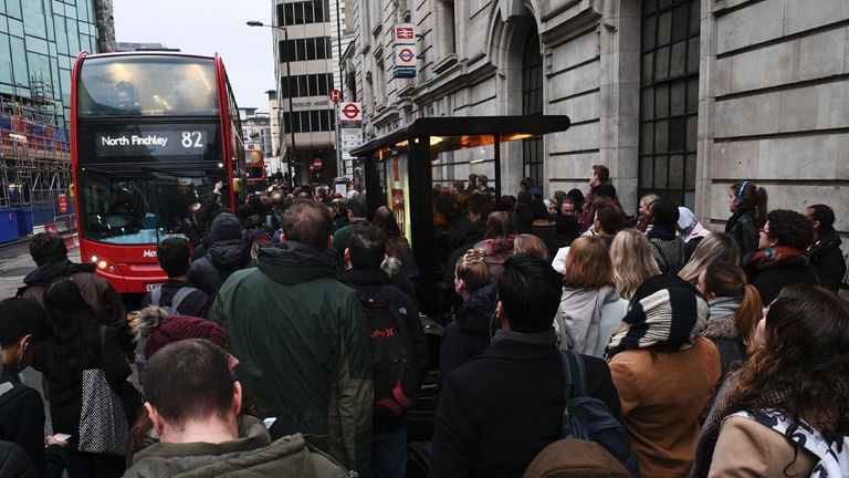 Commuters wait to board a bus at a bus stop near to Victoria station