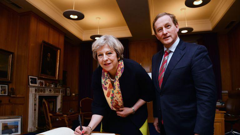 Theresa May signs the visitors book watched by Irish Taoiseach Enda Kenny