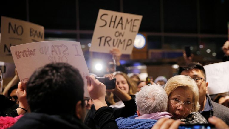 Democratic Senator Elizabeth Warren hugs a protester at Logan Airport in Boston