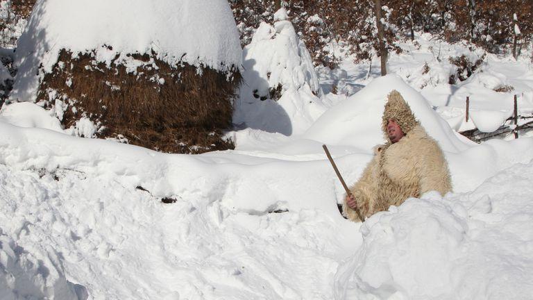 A man walks in the snow at around minus 26 degrees Celsius (minus 14.8 degrees Fahrenheit) in the village of Jezerc