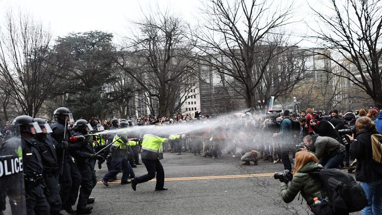 Police fire pepper spray at a large group of masked protesters