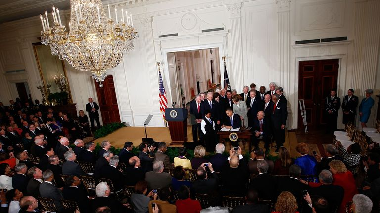 Barack Obama signs the health care bill