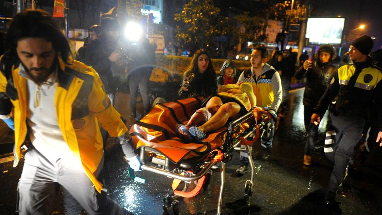 An injured woman is carried to an ambulance