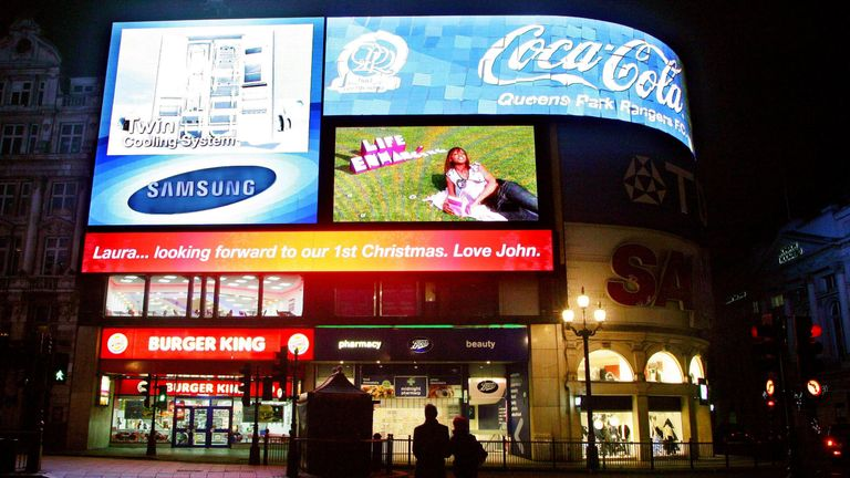 A couple stop to admire the first personal message posted on the new Piccadilly Lights sign