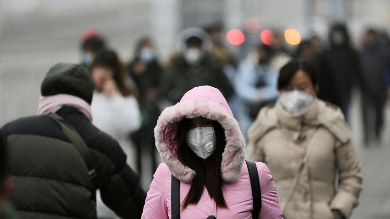Woman wearing mask walk toward Beijing office building during the smog