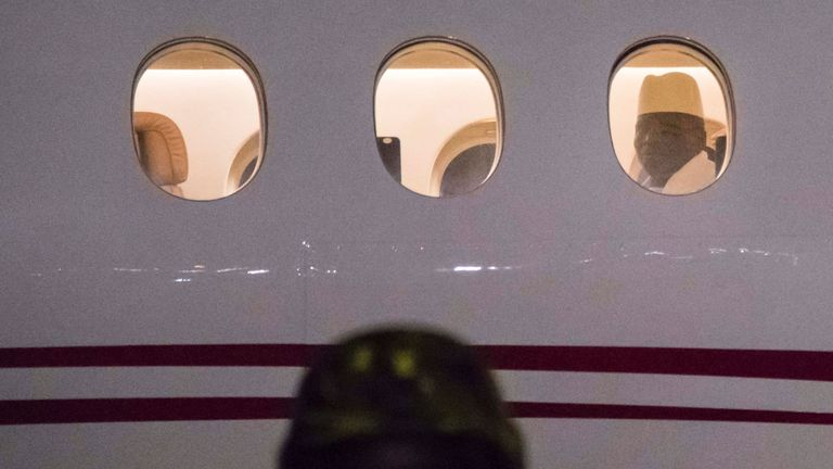 Mr Jammeh looks through the window of his plane as he leaves his country