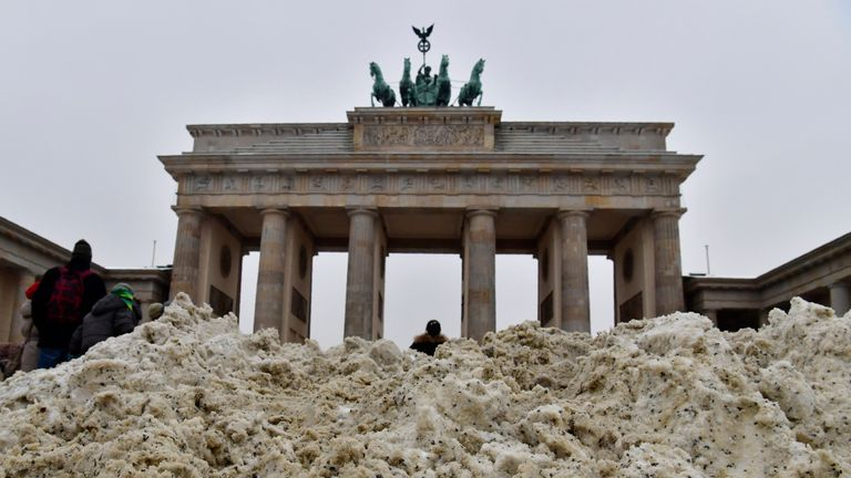 A child plays in a pile of snow shovelled together in front of the Brandenburg Gate in Berlin
