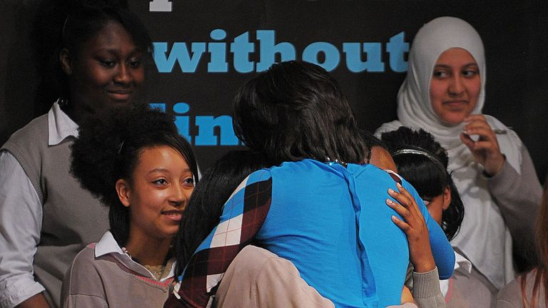 Michelle Obama hugs pupils at the Elizabeth Garrett Anderson school in London