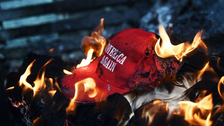 A 'Make America Great Again' hat is set alight during an anti-Trump protest