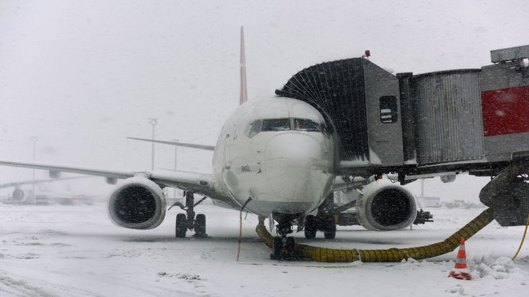 A Turkish Airlines plane is covered by frost and snow during snowfall at Ataturk international airport in Istanbul